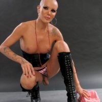 Bald TS pornstar Blondie Johnson letting big dick loose from panties in long boots