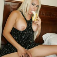 Blonde tranny Afrika Kampos frees her big tits and cock from a long dress