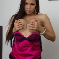 Asian ladyboy Vitress Tamayo freeing large tits and shecock from lingerie