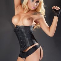 Blonde shemale Angeles Cid flaunting big tits in bustier and stockings