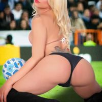 Tattooed blonde shemale babe Angeles Cid exposing large tits in stripper boots