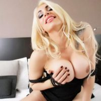 Beautiful blonde shemale Angeles Cid flaunting huge trans boobs in long boots