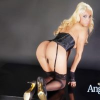 Beautiful Mexican shemale Angeles Cid displaying big tits in black lingerie and heels