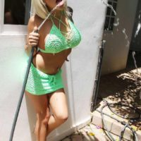 Blonde Mexican tranny Angeles Cid wetting huge boobs outdoors in high heels