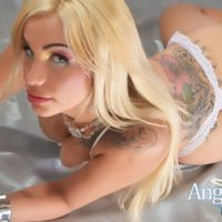 Blonde trans model Angeles Cid posing seductively in white bra and thong panty set