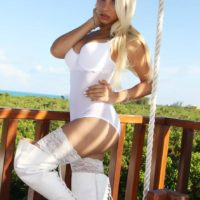 Blonde shemale pornstar Angeles Cid exposing big tits outdoors in stripper boots
