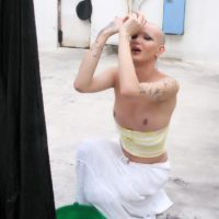 Clothed tranny Blondie Johnson letting big cock loose outdoors while doing laundry