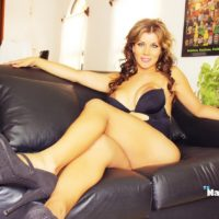 Latina tranny Naomi Chi releasing large tits and cock from dress on leather couch