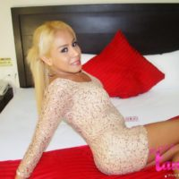 Pretty blonde shemale Tania Quintanilla modeling non nude on bed in high heels