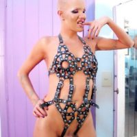 Tatted shemale model Blondie Johnson modeling solo in mask and fetish garb