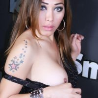 Tattooed shemale model Nina Stronghold baring big tits in black pantyhose