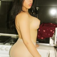 Busty brunette ladyboy Vivian Black showing off sexy ass and big cock in kitchen