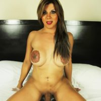 Solo brunette tranny Naomi Chi baring big boobs and large shecock on bed
