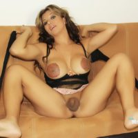 TS pornstar Naomi Chi letting big boobs loose from lingerie in sexy black stockings
