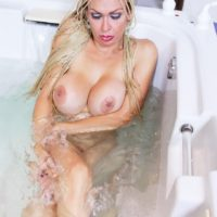 Beautiful blonde shemale showing off large tits and nice ass in the bathtub