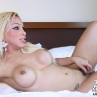 Long legged blonde shemale showing off bare ass and shaved shecock on bed