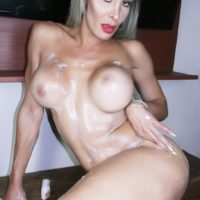 Nude shemale Nelly Ocho rubs lotion into her big tits and hung tranny cock