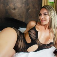 Shemale solo model Nelly Ochoa poses on her bed wearing a sheer bodystocking