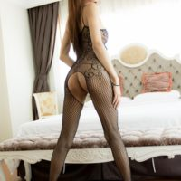Solo ladyboy model Bell masturbates wearing a mesh bodystocking and heels