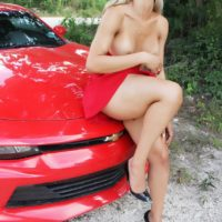 Blonde shemale Nelly Ochoa flashes her upskirt cock and big tits atop a sports car
