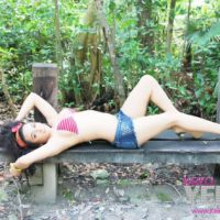 Teen tranny Keira Verga models on an outdoor bench in bikini top and shorts