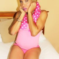 Blonde tranny Percy Princess holds her big boobs prior to masturbating on her bed