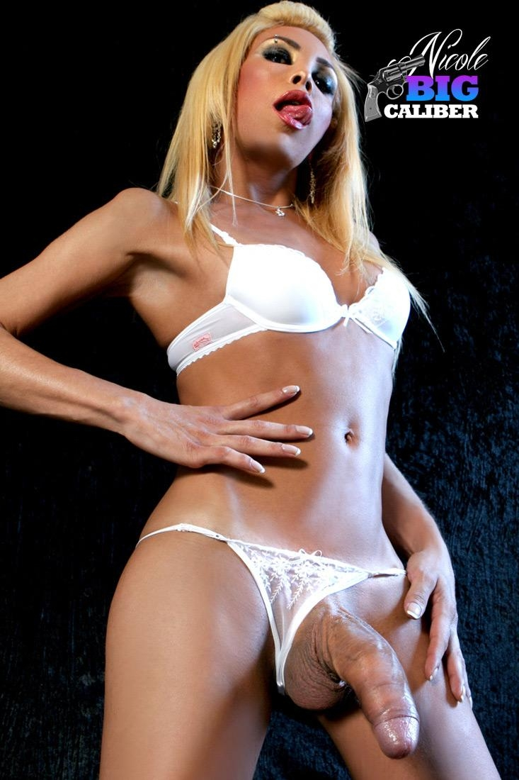 Blonde transsexual model Nicole Big Caliber pulls her huge cock out of her white panties