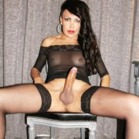 Brunette tranny Nicole Big Caliber jerks off her large cock in black stockings and heels