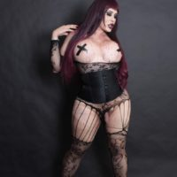 Fat shemale Sina Latina exposes her big boobs in a corset and stockings