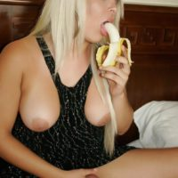 Solo shemale Afrika Kampos eats a banana while stroking her cock on her bed