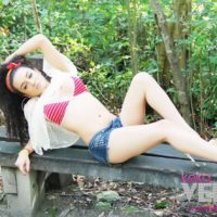 Teen shemale Keira Verga models non nude in bikini top and shorts on outdoor bench