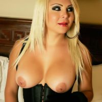 Blonde TS solo girl Afrika Kampos flaunts her big tits in black corset and gloves