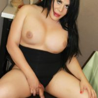 Chubby shemale Sina Latina displays her big boobs while masturbating on a chair