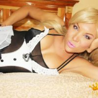 Blonde shemale Percy Princess frees her firm tits from sensual lingerie in black stockings
