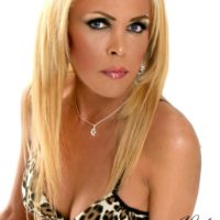 Blonde shemale Nicole Big Caliber takes off bra and panty set to model totally naked