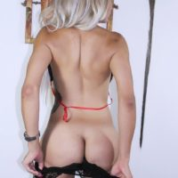 Blonde shemale Percy Princess exposes big tits and ass as she removes bikini and nylons