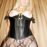 Hot blonde tranny Afrika Kampos shows her big tits in leather corset and pantyhose