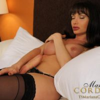 Beautiful shemale Mariana Cordoba strokes her huge cock in stockings on her bed
