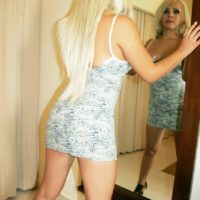 Sexy blonde shemale Afrika Kampos exposes her big tits and cock in front of a mirror