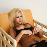 Blonde shemale Milla Viasotti bares her big tits and shaved cock on a chair