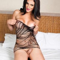 Busty shemale babe removes see thru lingerie before jerking her big cock on a bed