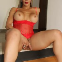 Leggy tranny Nelly Ochoa frees her big tits and ass from red lingerie and her cock too