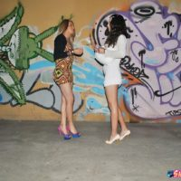 Shemale hookers flash their bare asses in front of a graffiti covered wall outdoors