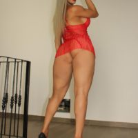 Bare legged tranny Nelly Ochoa exposes her big tits and cock in red lingerie and heels