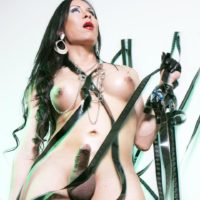 Dark haired trans woman strokes her big cock in a bondage harness and OTK boots