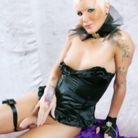 Tall blonde shemale Blondie Johnson pulls out her hard cock wearing a black corset