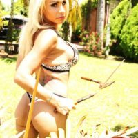 Blonde trans woman Angeles Cid frees her big tits from a bra while gardening in yard