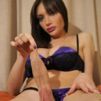 Dark haired shemale Mariana Cordoba plays with her massive cock in OTK boots