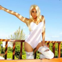 Hot blonde tranny Angeles Cid dildo fucks her ass while totally naked on a deck