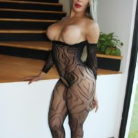 Platinum blonde tranny Nelly Ochoa frees her big tits from a crotchless bodystocking